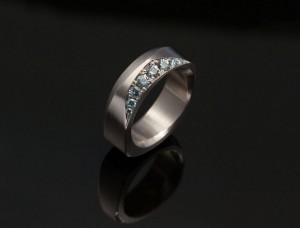 En geometrisk vigselring av Petronella. Tillverkad i vitguld med etiska ljusblå safier och små färgade diamanter satta med fadenfattning.