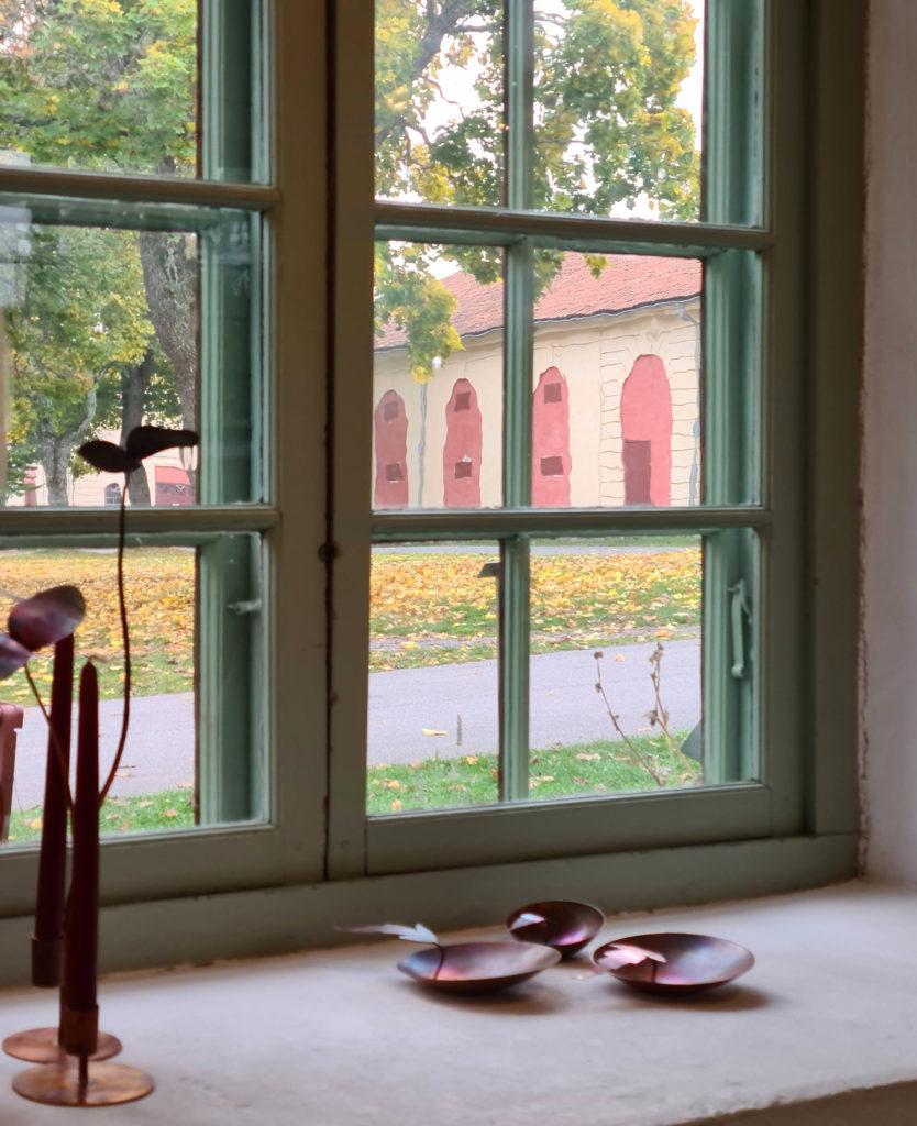 Utställning bland höstlöv och metallkonst Fönstervy av ljusstakar och skålar i koppar av Pernilla Sylwan från LODs utställning på Sadelmakarlängan.
