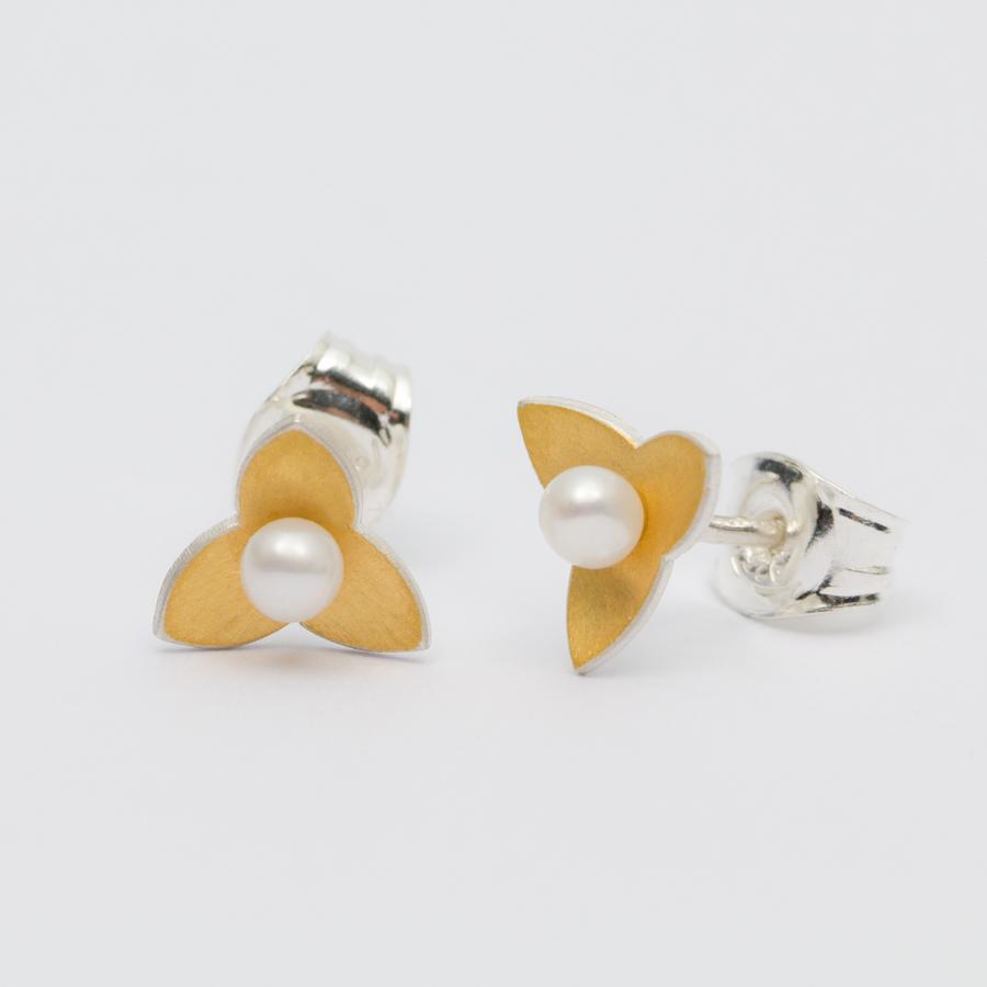 Små örhängen i silver, oxiderat silver och silver med keumboo, silver täckt av en tunn plåt med 24k guld. Mitti berlockerna sitter vita sötvattenpärlor eller svarta kulor av hematit. Pärlor/kulor är 3 eller 2 mm i diamete. Formen kommer från blommorna på dvärgmåra.