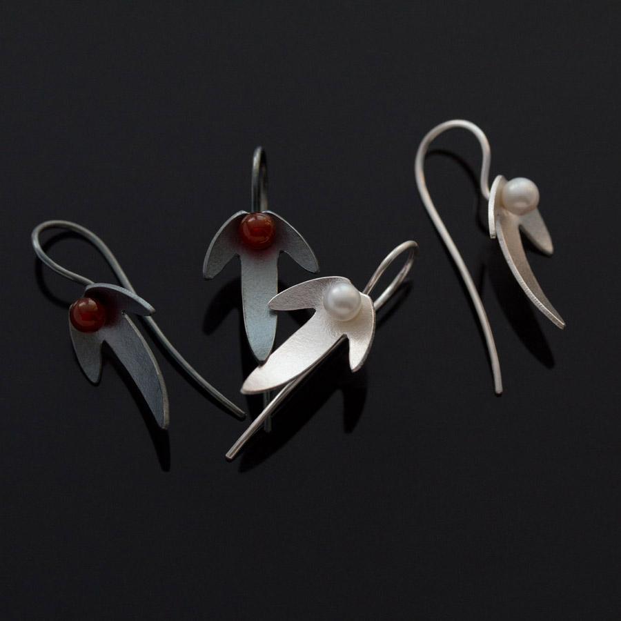 Örhängen i oxiderat silver i form av avenboksfrukter. i mitten röd carneol respecktiva blnaksvart hematit.