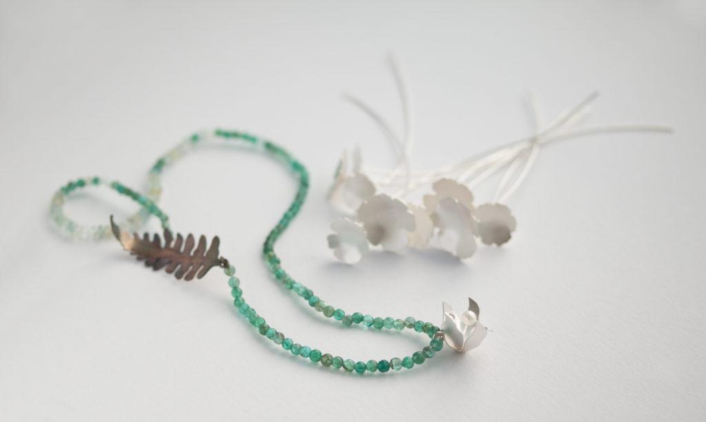 """""""Växter"""" utställningen förlängd till den 2474. halsmycke med vit skogslija av silver, pärla, apatita och akvamarin. Örhängen i form av spikblad i silver."""