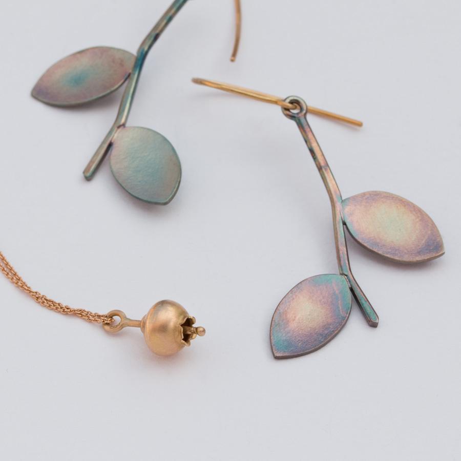Örhänge  blåbärsblad i oxiderat silver och guld, hängsmycke blåbärsblomma i 18k guld.