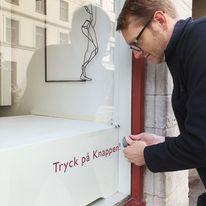 Erik lagar knappen i LODs lilla fönster. I bakgrunden en av Annas skulpturer.